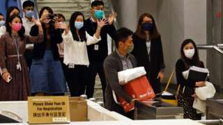 i-Cable TV news journalists leave with their boxes after being laid off in Hong Kong, China December 1, 2020。