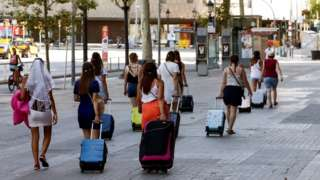 Tourists drag luggage through Barcelona