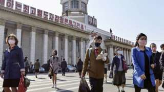 People wear face masks in front of Pyongyang Station in Pyongyang, North Korea (27 April 2020)