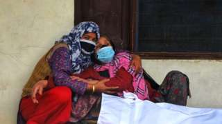 Women mourn the death of a family member in India