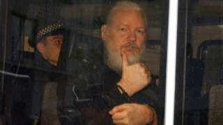 Assange gestures with a thumbs up after he was arrested by Met Police officers at Ecuador's embassy in London
