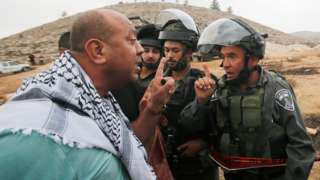 A Palestinian protester argues with an Israeli border policeman near Hebron in the occupied West Bank (15 November 2019)