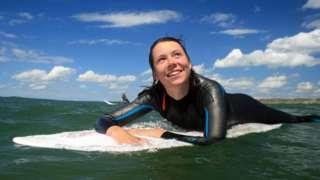 A woman surfing in Llangennith, Gower