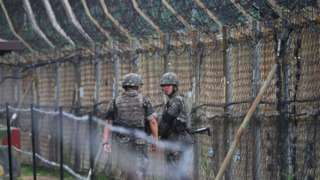 South Korean soldiers patrol along a fence in the Demilitarized zone