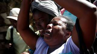 Women react after a fire destroyed part of an orphanage, in Port-au-Prince, Haiti, 14 February, 2020.