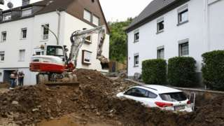 A digger clears debris in Germany after flooding, 15 July 2021