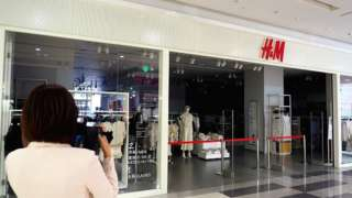 People walk past a closed H&M store in Jinan, Shandong Province of China