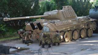 A World War Two Panther battle tank is made ready for transportation from a residential property in Heikendorf, Germany, 2 July 2015