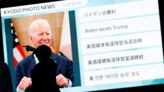 """Passersby are silhouetted against a big screen showing reports on Joe Biden""""s U.S. presidential election victory in Tokyo"""