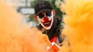 A protester wearing a mask is seen amongst smoke as French Labour unions demonstrate against the government's pensions reform plans, 5 December 2019