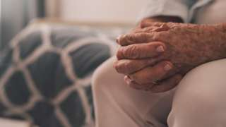 Elderly woman sitting with her hands clasped in a retirement home