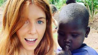 Stacey Dooley in Uganda, posing with a young child