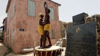 "A statue commemorating the abolition of slavery stands in front of the House of Slaves museum, before being relocated to the ""Freedom and Human Dignity"" Square, on Goree island, off the coast of Dakar, Senegal July 3, 2020"
