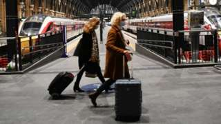 Commuters at Kings Cross train station in London, Britain, 20 December 2020.