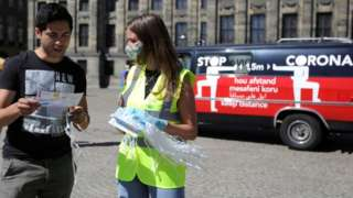 A woman hands out masks and information brochures in Amsterdam, Netherlands August 5, 2020