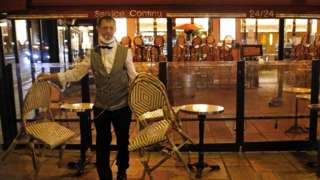 A barman closes his establishment at 9pm as part of a city-wide night time curfew during the coronavirus (COVID-19) pandemic on October 28, 2020 in Paris, France.