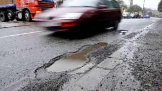 Car drives past a pothole