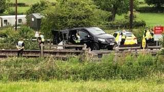 A black van was struck by a train near Welshpool