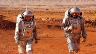 Two astronauts walk in spacesuits during a training mission for planet Mars at a site that simulates an off-site station at the Ramon Crater in Mitzpe Ramon in Israel's Negev desert, on 10 October 2021
