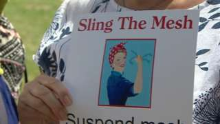 A woman holding a poster that reads: Sling the mesh