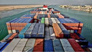 View across the deck of a container ship entering the Suez Canal, Egypt, (with the city of Suez at upper right)