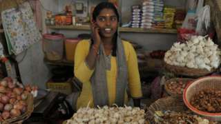An Indian woman talks on her mobile phone at a vegetable market in Hyderabad