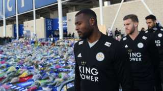 Wes Morgan looks at the floral tributes left to the victims of the helicopter crash which killed Leicester City's Thai chairman Vichai Srivaddhanaprabha, outside the King Power Stadium