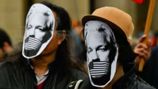 Demonstrators protest with masks of WikiLeaks founder Julian Assange during a Pro-Assange demo in Germany