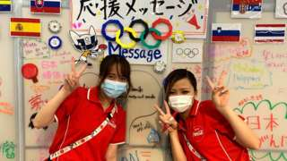 Two volunteers pose behind a wall with handwritten messages to cheer on Olympic athletes