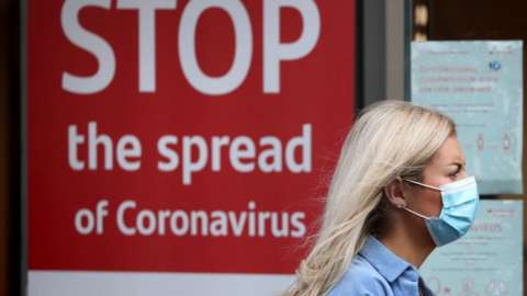 A woman wearing a mask walks past a sign that reads: Stop the spread of coronavirus