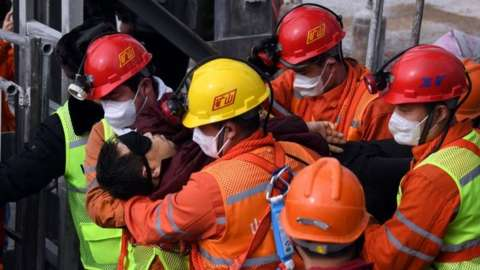 A picture released by Xinhua News Agency shows a trapped miner being lifted from a gold mine in Qixia City, east China's Shandong Province, 24 January 2021.