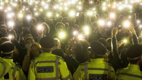 Police attend a vigil for Sarah Everard on Clapham Common in March 2021