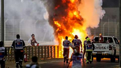 Rescuers run toward's F1 driver's car, which is on fire