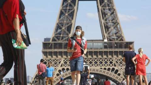 Tourist in front of Eiffel Tower with mask on