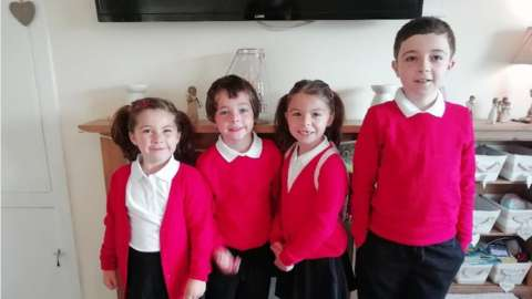 Four children from a family pose together