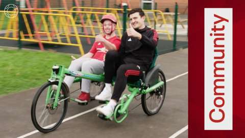 Harry Maguire on a bike with a young person