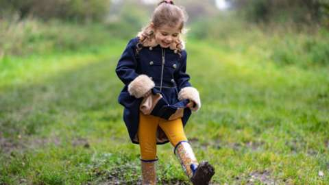 A little girl playing in a muddy puddle