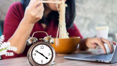 A woman eating noodles wit a clock in the foreground