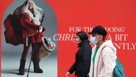 Shoppers walking past a Christmas window display in a store on Oxford Street, London