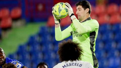 Thibaut Courtois makes a save for Real Madrid