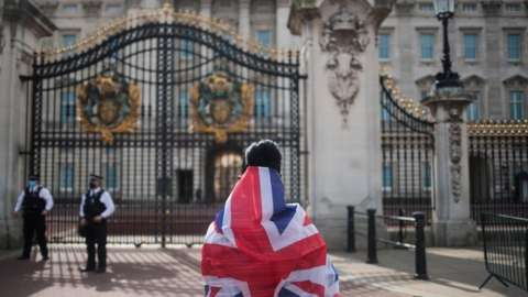A person holds a flag while looking to Buckingham Palace after it was announced that Britain's Prince Philip, husband of Queen Elizabeth, has died at the age of 99, in London, Britain,