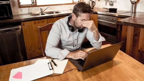 A man rubs his eyes in apparent stress as he sits at a wooden kitchen table with a laptop and papers
