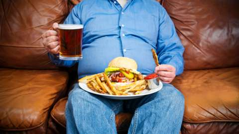 Overweight man over-eating on a couch -