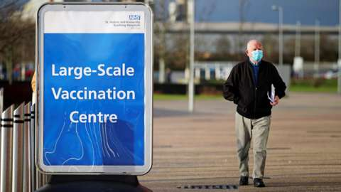 A man walks past a sign outside the mass vaccination centre at the Totally Wicked Stadium
