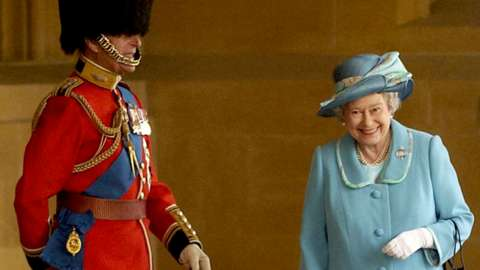 The Queen giggling as she passes Prince Philip