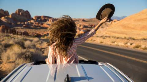 Woman standing out of sun roof