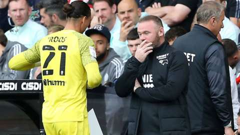 Derby boss Wayne Rooney watches keeper Kelle Roos leave the pitch after being sent off