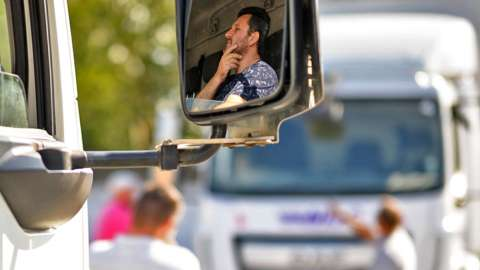 A student looks on from the cab of an HGV lorry as another man takes part in a driving lesson at the NDC heavy goods vehicle training centre on 22 September 2021 in Croydon, England