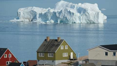 An iceberg near a village in Greenland