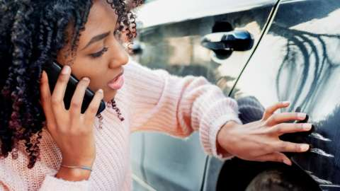 A woman calling her insurer after scratching her car